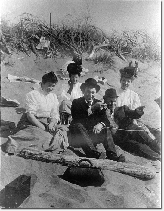 A couple of swells with their sweethearts picknicking in the sand at Ocean Beach, c. 1910.